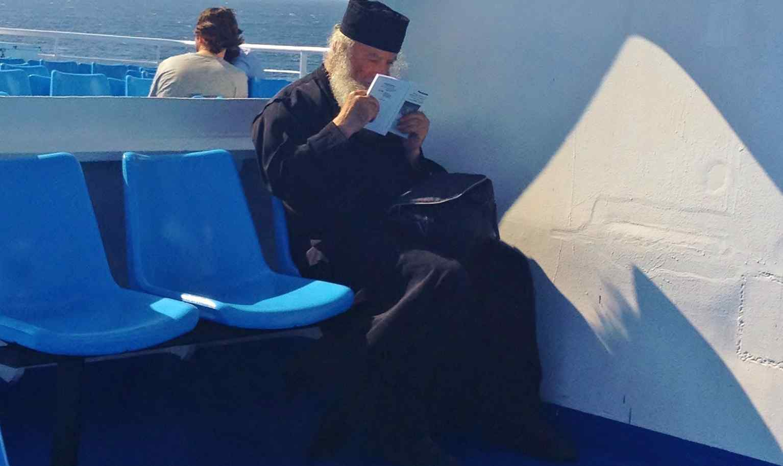 Orthodox Priest Reading On-board a Greek Ferry KALIMERA travel Gallery